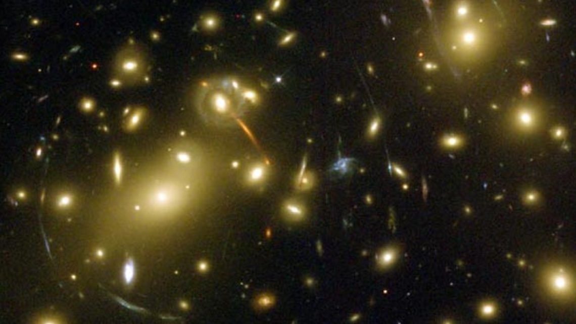 Photo of DEC examining gravitational lensing, or the warping of light from background objects around massive objects foreground