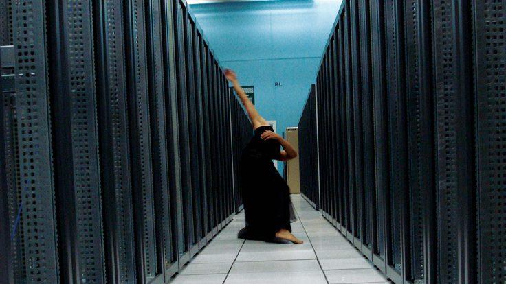 Ben Wegman moves down an aisle of server racks at CERN's Computer Center.