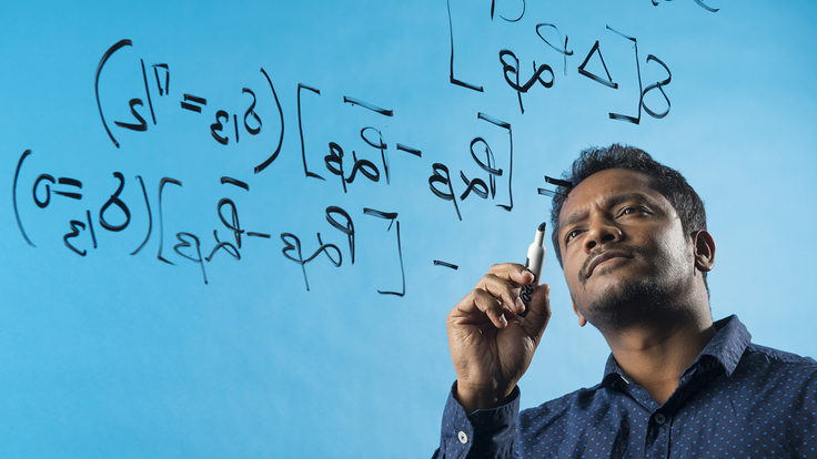 Jogesh Rout writing equations on a clear panel. The background is blue.
