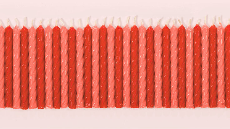 Row of red and pink candles with pink background