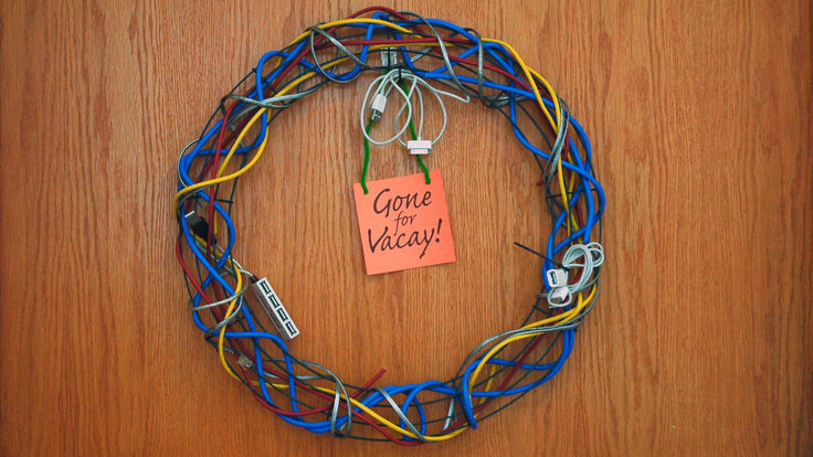 "Wreath made of computer cables and post it note reading ""Gone for Vacay"""