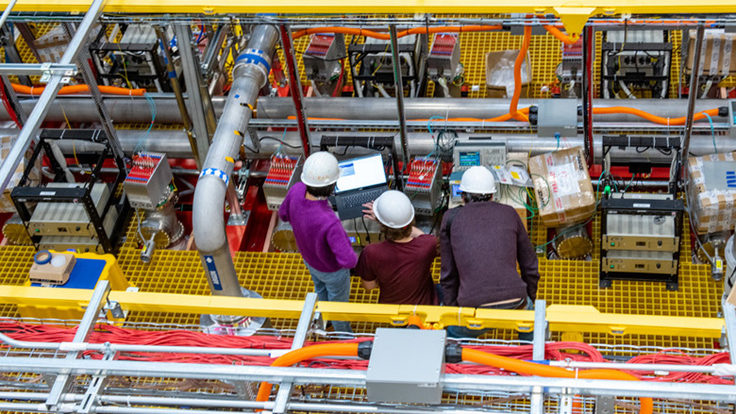 Three scientists in white hard hats working on the ICARUS detector, photographed from above.