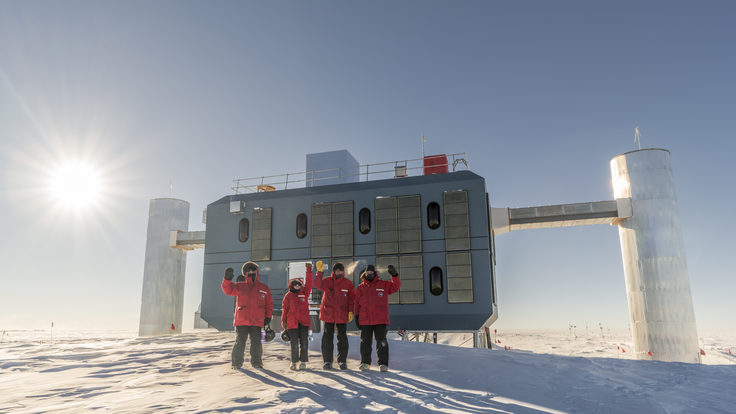 Photo of four researchers in red coats standing on white snow at the South Pole in front of a building