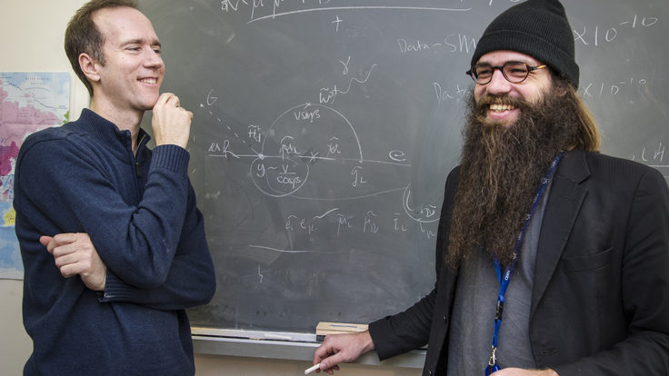 Photograph of scientist James Wells with artist Julius von Bismarck in front of a chalkboard full of equations