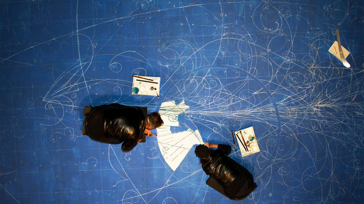 Overhead view of artists kneeling on a blue surface and creating an image of bubble chamber tracks with white sand