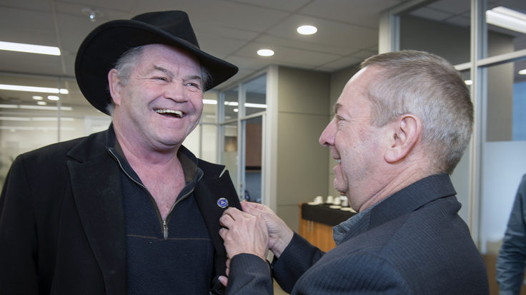 Fermilab Director Nigel Lockyer gives a smiling Micky Dolenz a Fermilab pin