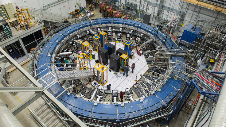 Overhead view of people working inside a room-sized blue ring, the Muon g-2 magnet