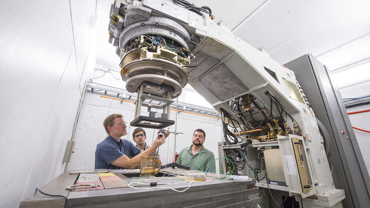 Tom Kroc, Matteo Quagliotto and Mike Geelhoed set up a sample beneath the A2D2 accelerator to test the electron beam.