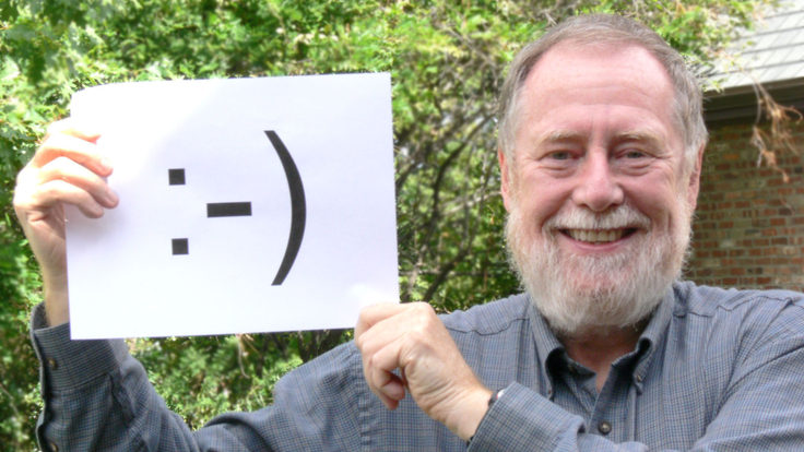 Photo of Scott Fahlman holding smiley face sign