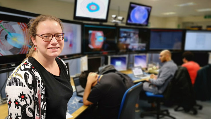 Image of a woman in glasses standing in front of several screens in a control room